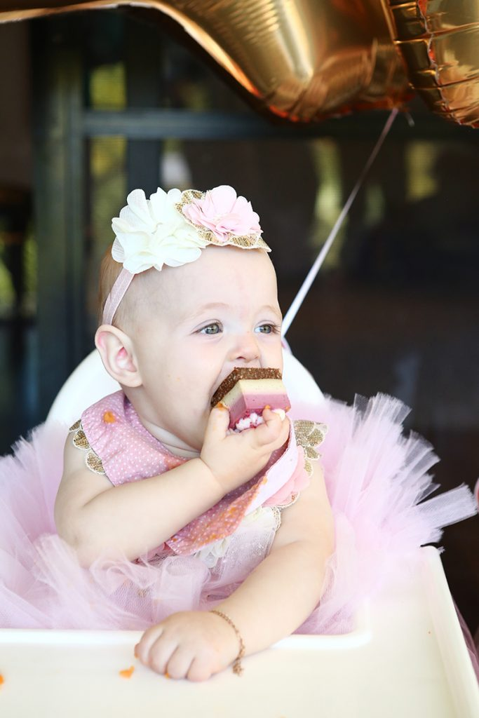 Baby girl eating raw vegan cake at birthday party