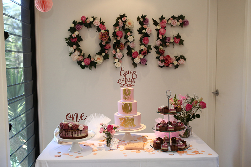 Three tier baby birthday cake with flower wall
