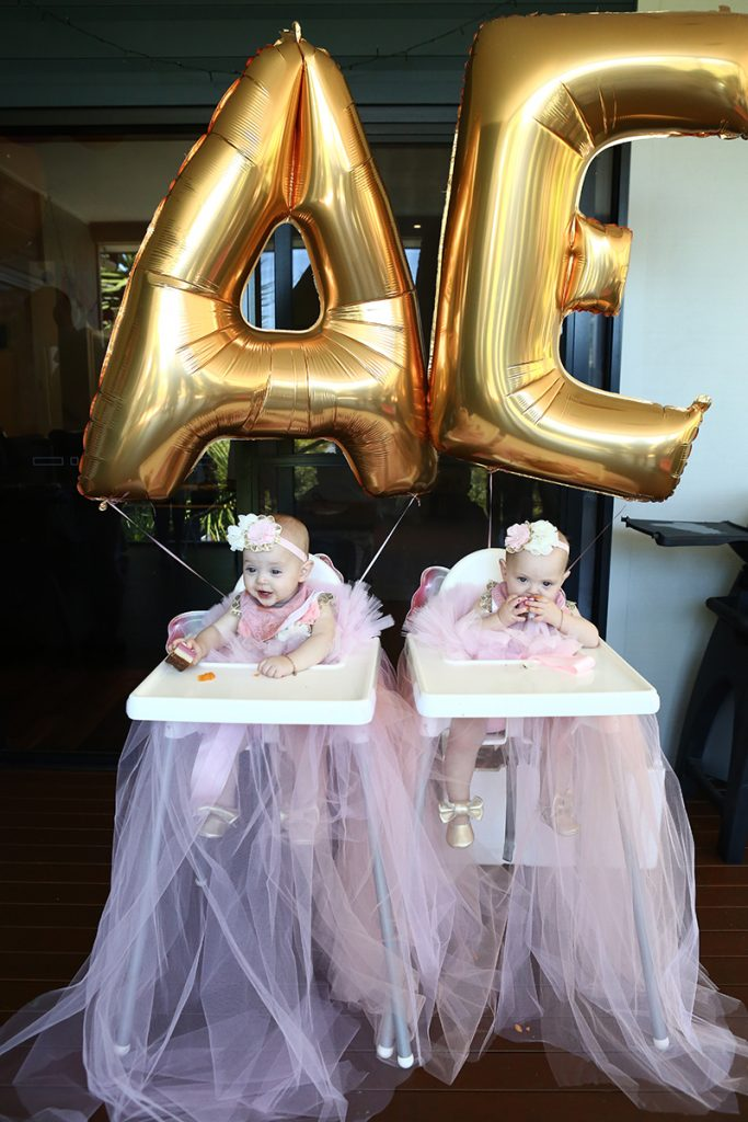 Gold balloons and baby twins at birthday party