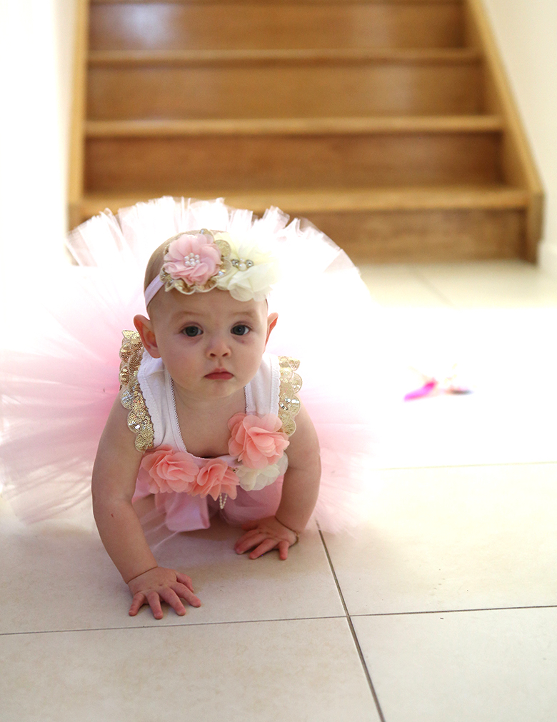 Sweet baby girl in pink tutu crawling on the ground