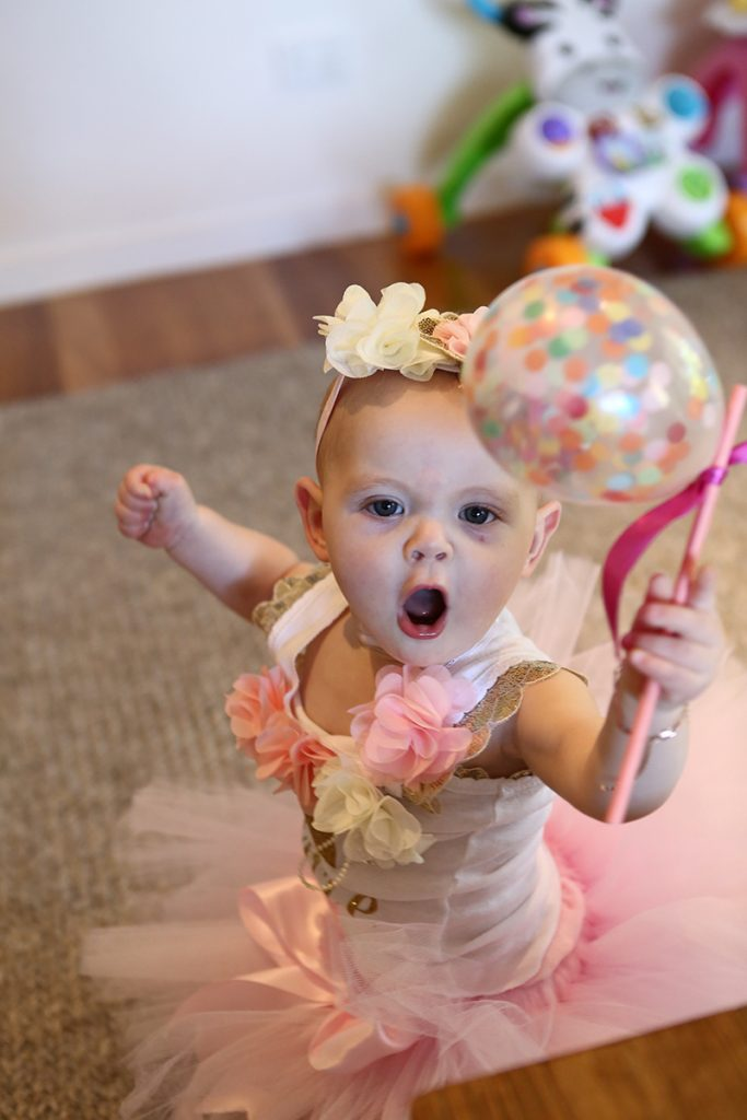 Cute baby girl in pink tutu looking at the camera holding a balloon