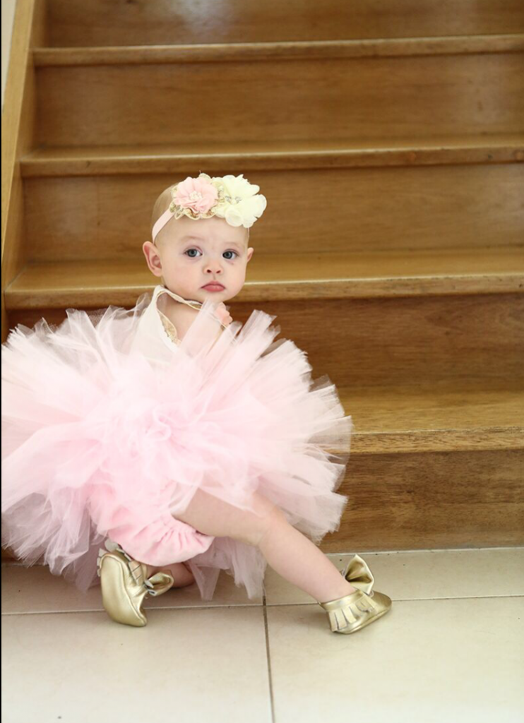 Baby girl on steps in a pink ballerina tutu