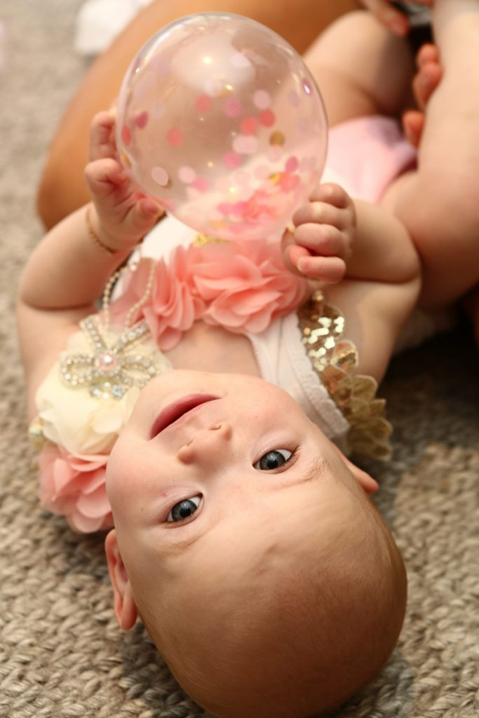 Cute baby girl lying on the floor smiling at the camera