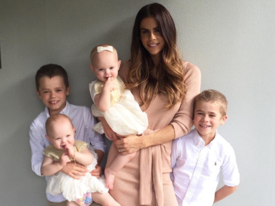 Sophie Guidolin and kids standing in front of a wall and smiling