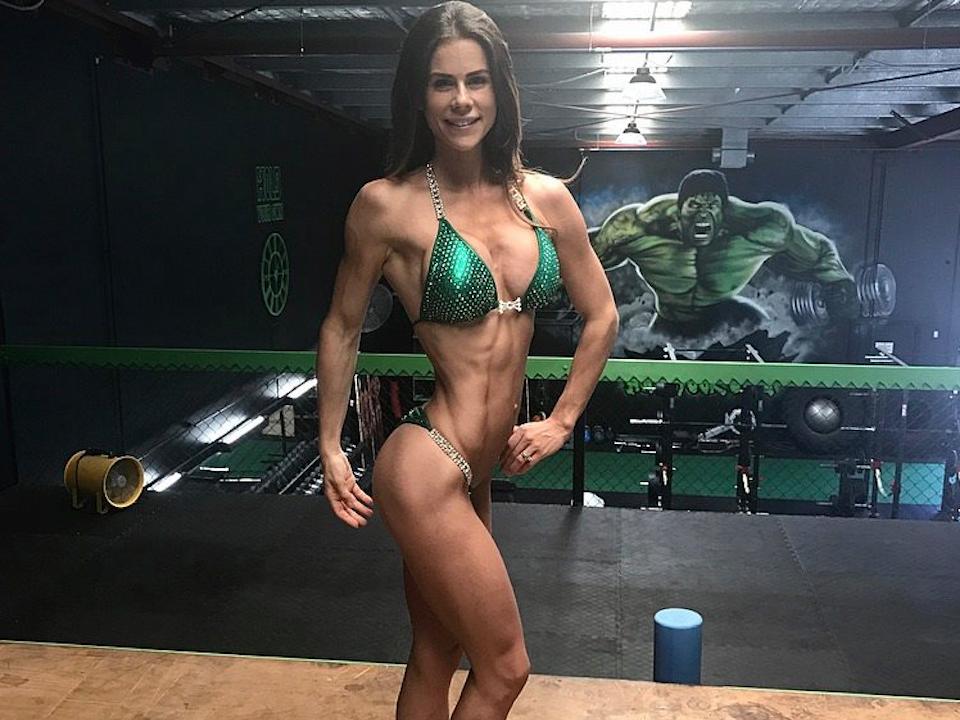 Fitness competitor in green bikini posing