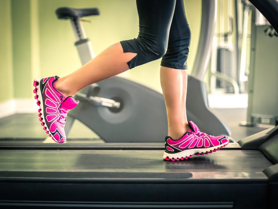 Girl with pink sneakers running on the treadmill