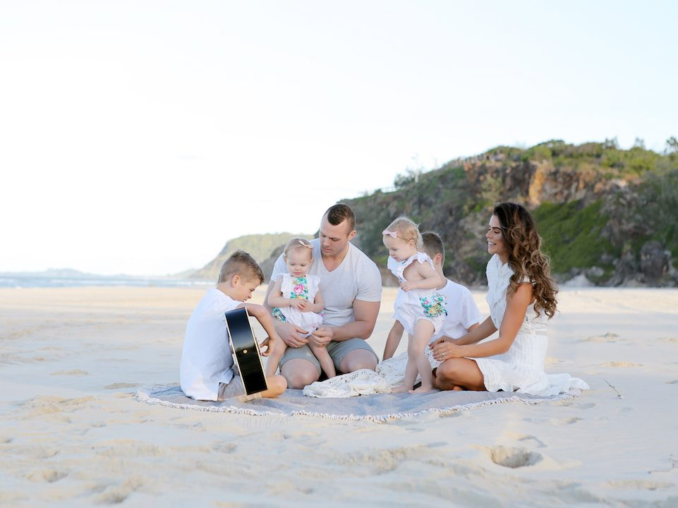 Four kids and parents at the beach wearing white