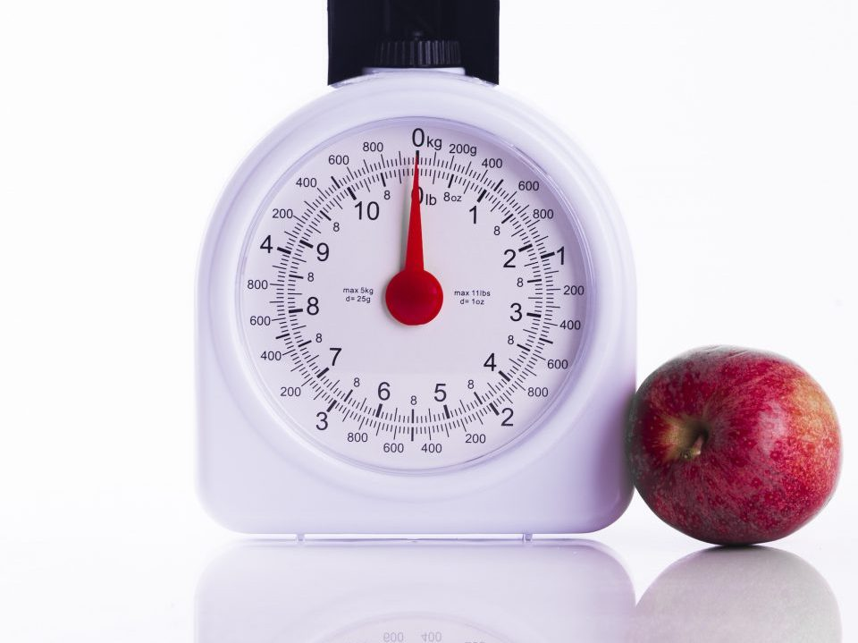 Red apples on kitchen scales on white background
