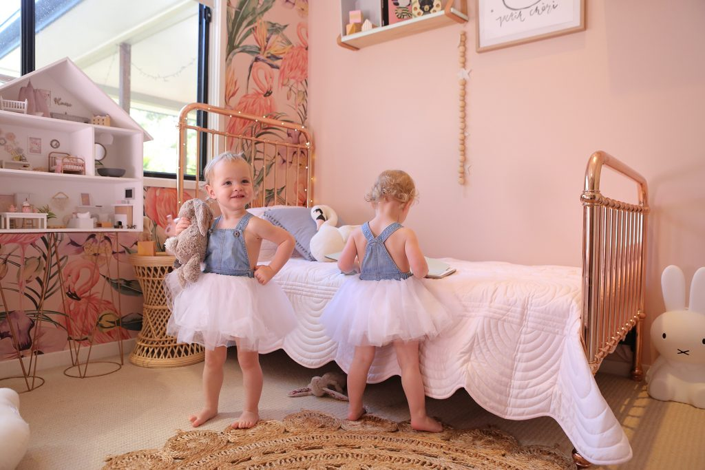 Baby girl twins in tutus in a pink bedroom