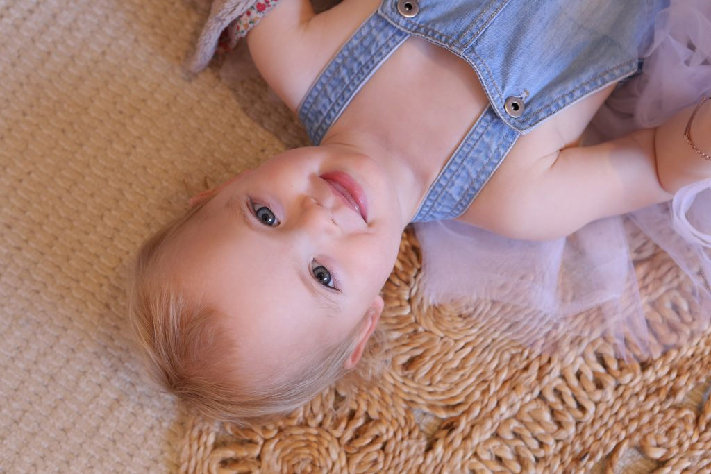 Baby girl smiling on the floor in denim overalls