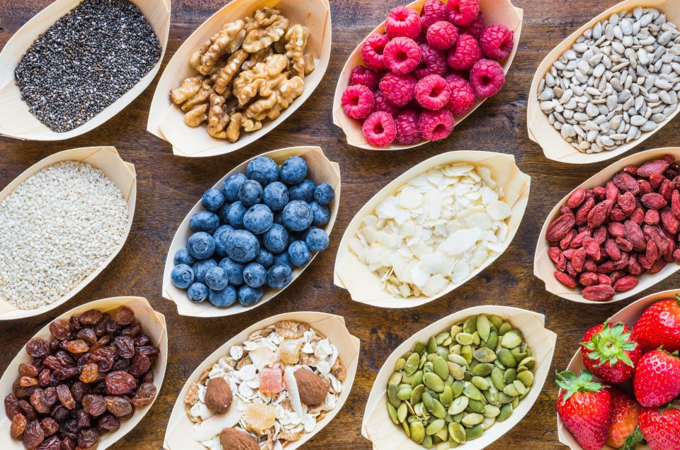Superfoods, berries, seeds, nuts, and fruits on wood background