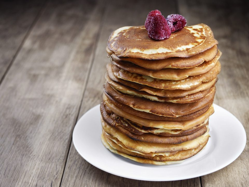 Pile of pancakes with berries in the white plate on the wooden table