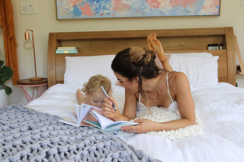 Sophie Guidolin and baby lying on the bed reading a book together
