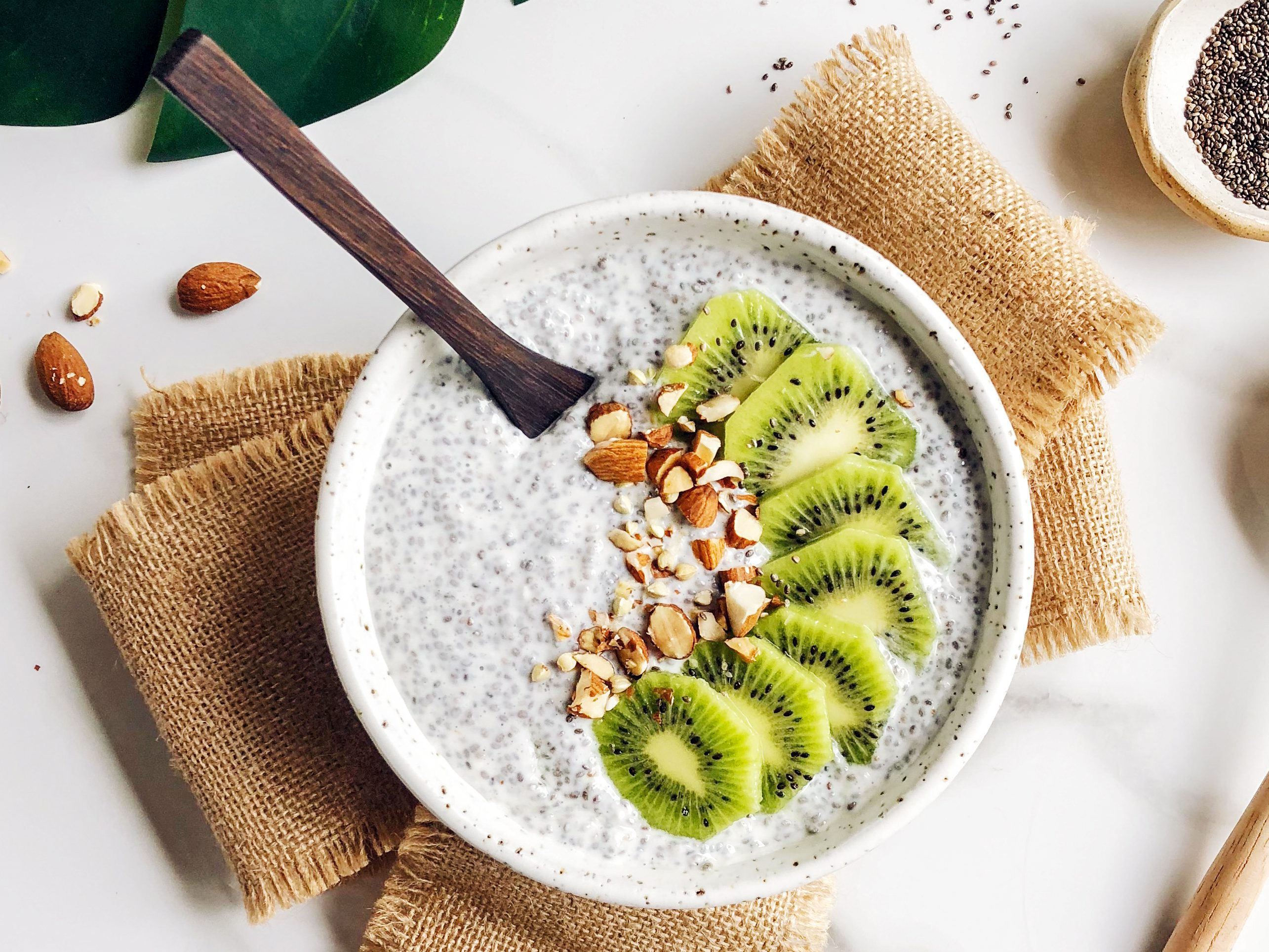 Chia seed pudding from Sophie Guidolin recipes with kiwi and crushed nuts in a white bowl
