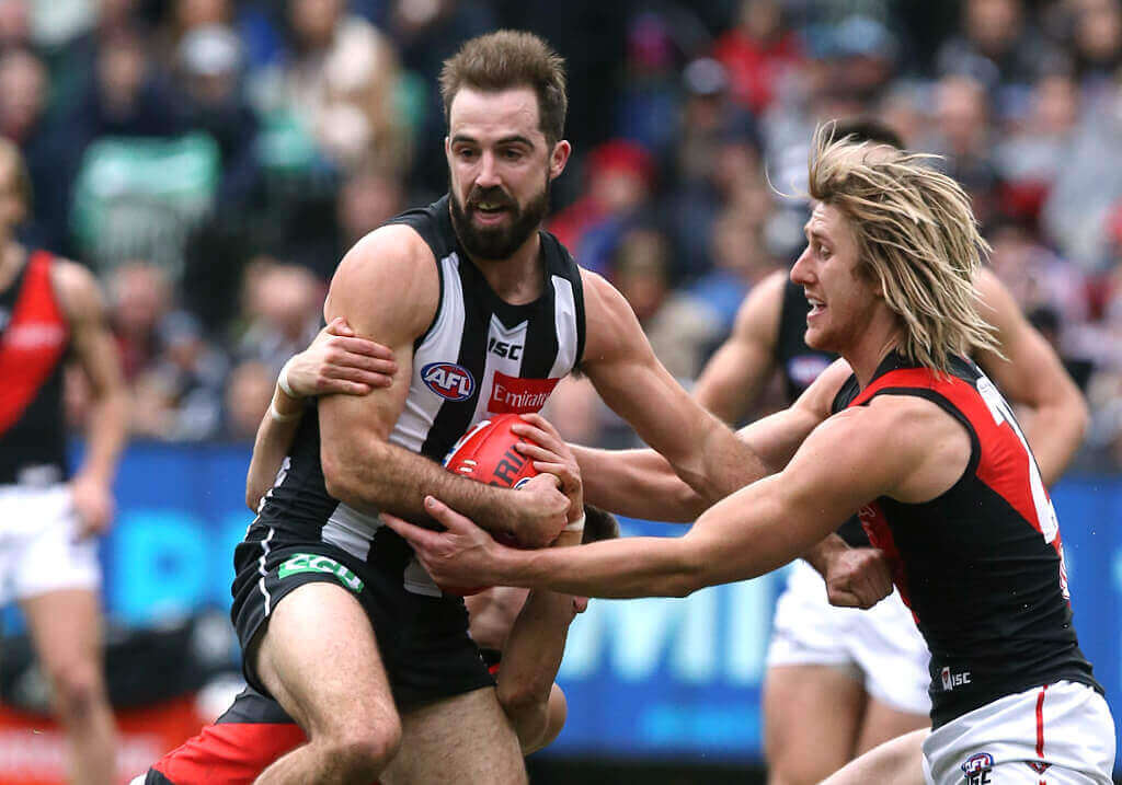 Magpie Steele Sidebottom tackled by Dyson Heppell