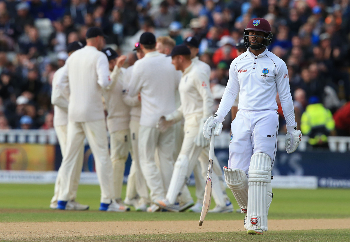 West Indies' Shai Hope (R) walks back to the pavilion after losing his wicket during play on day 3.
