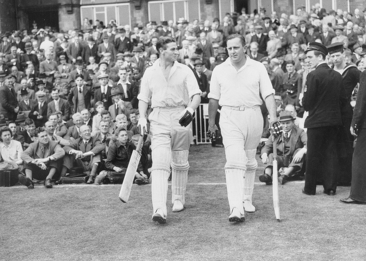 Keith Miller (left) and Cec Petter go out to bat in a Victory Test in 1945