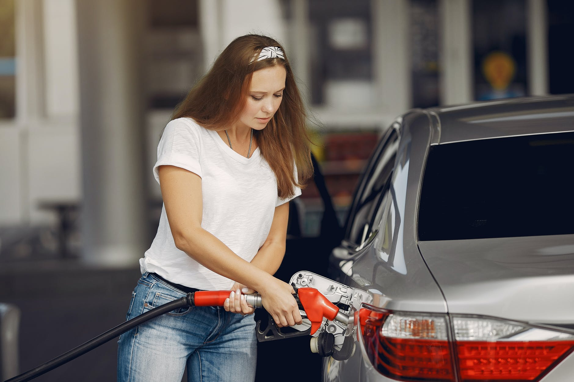 focused young woman refueling car