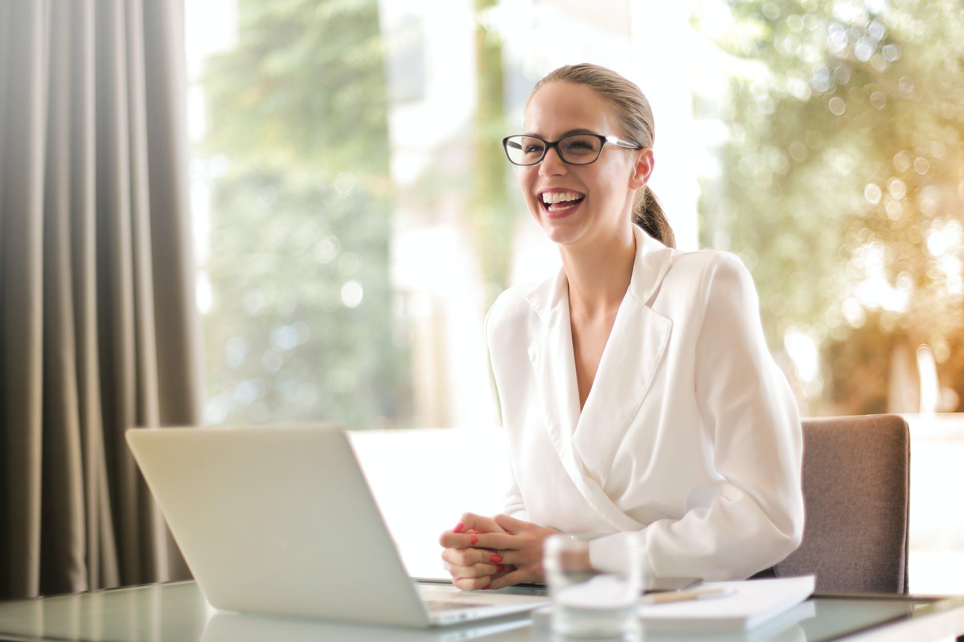 pengusaha wanita yang tertawa bekerja di kantor dengan laptop