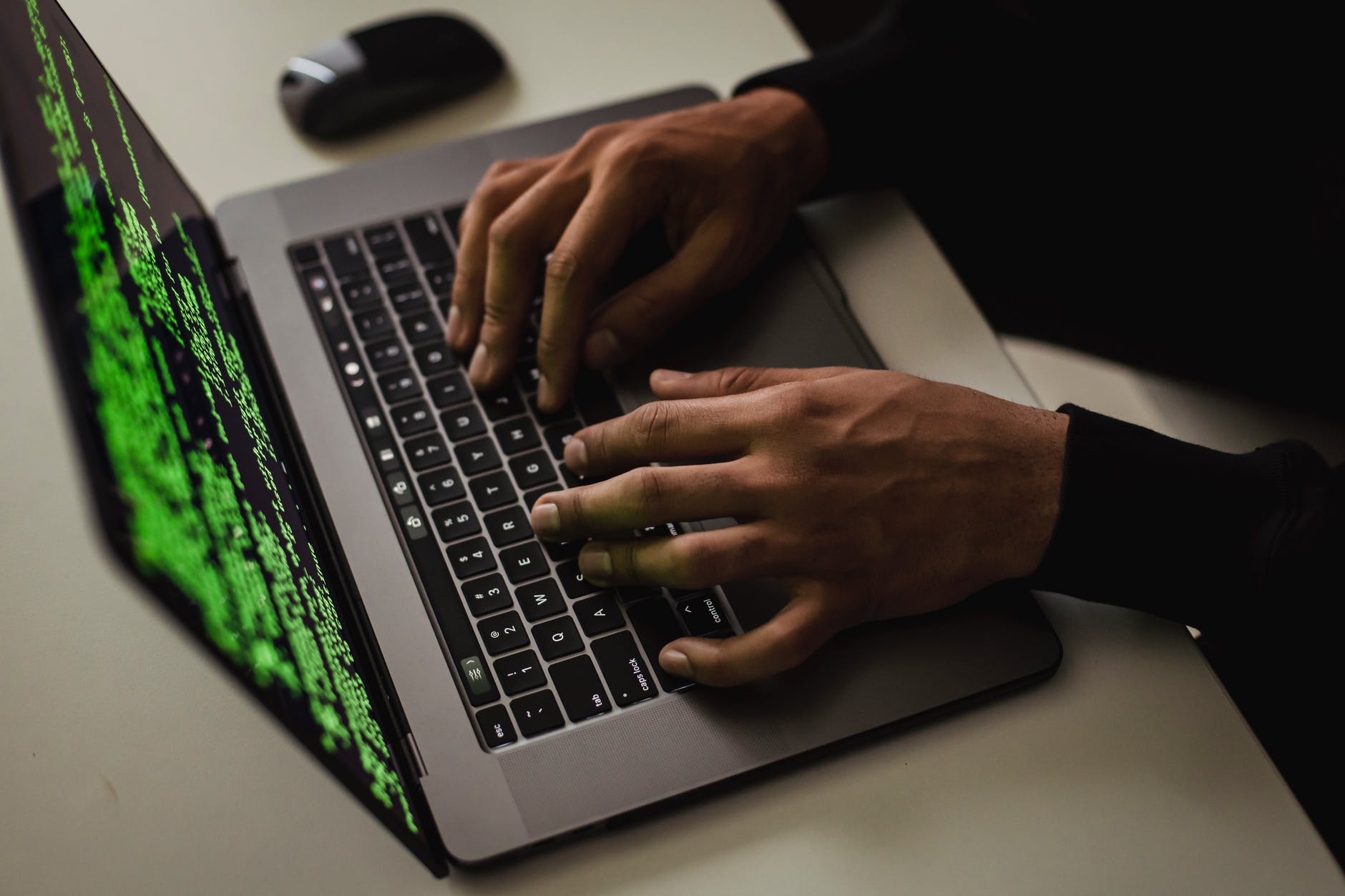crop cyber spy hacking system while typing on laptop