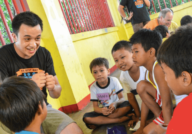 Bradley teaching Filipino kids. Photo by Wellington Andersen Co.