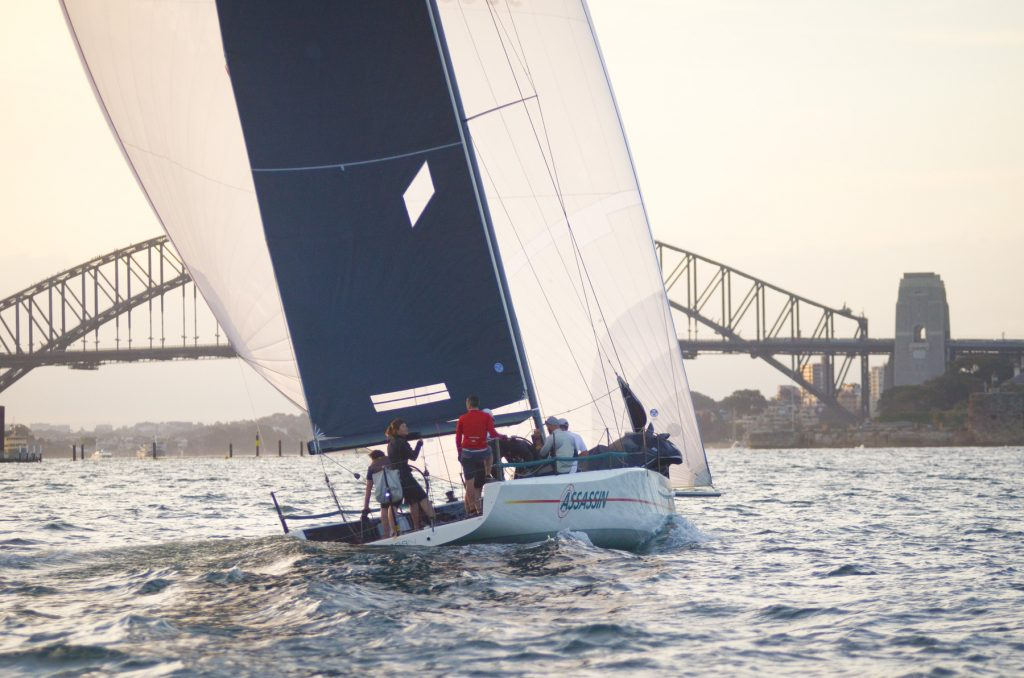 mc38 assassin sailing on sydney harbour with bridge at the back