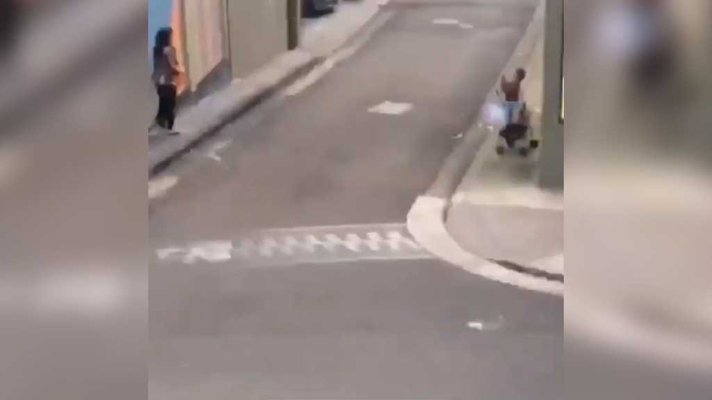 Mother poses as toddler takes photo from pram