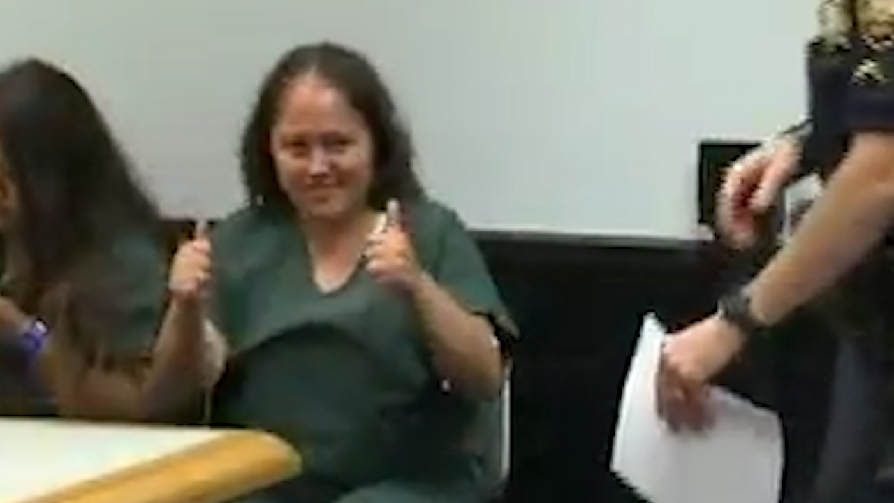 Mother accused of fatally stabbing family gives thumbs-up in court