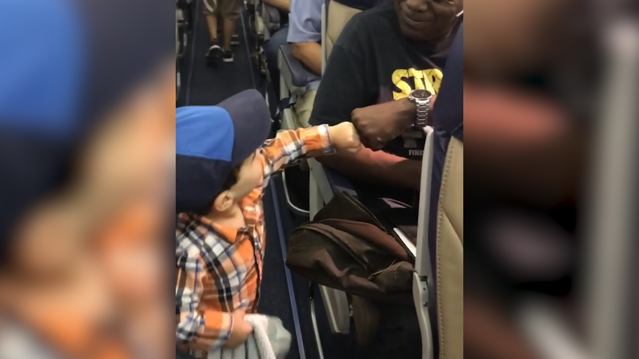 Cute toddler fist bumps every passenger while boarding