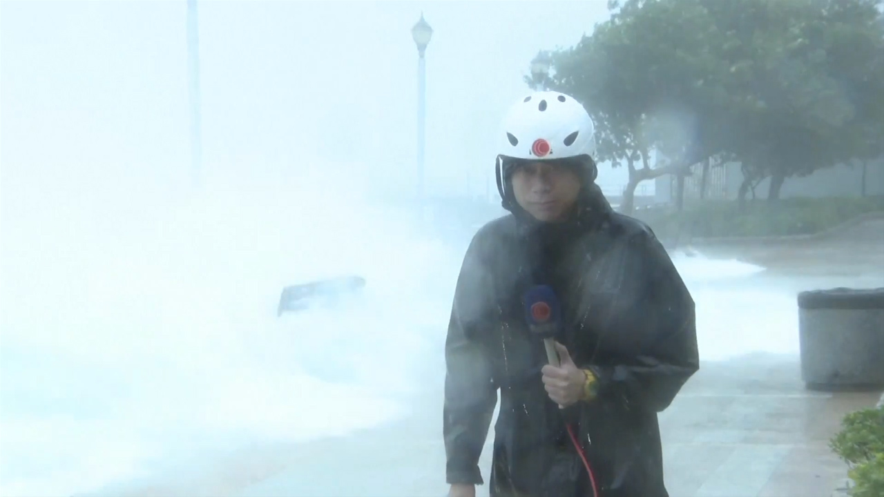 TV reporter knocked off his feet by wave