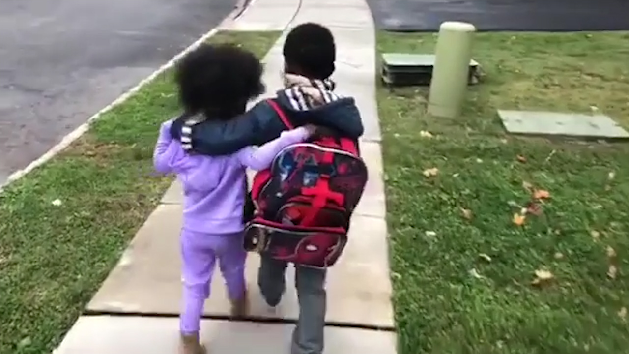 Brother walks sister home after school