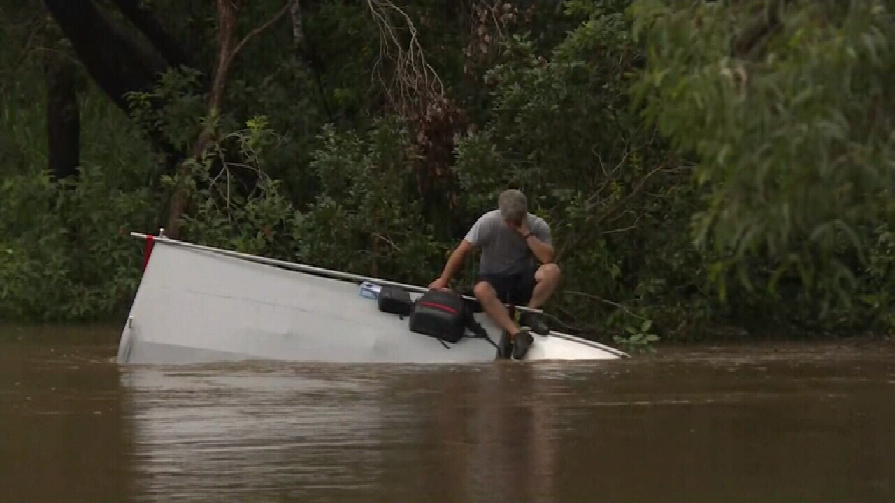 Driver stuck on car roof after driving into floodwaters