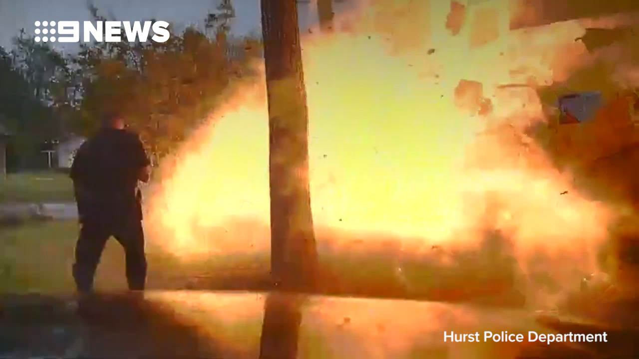 Moment home explodes nearly killing police officer