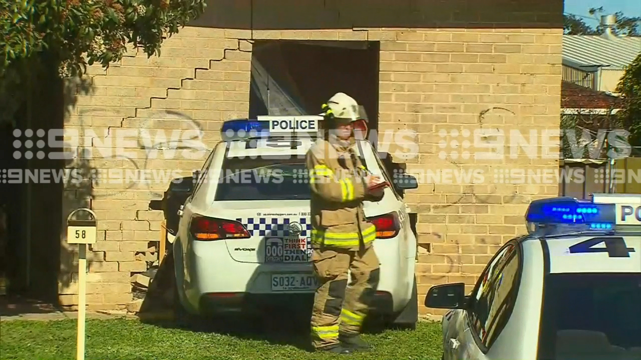 Police car drives into home