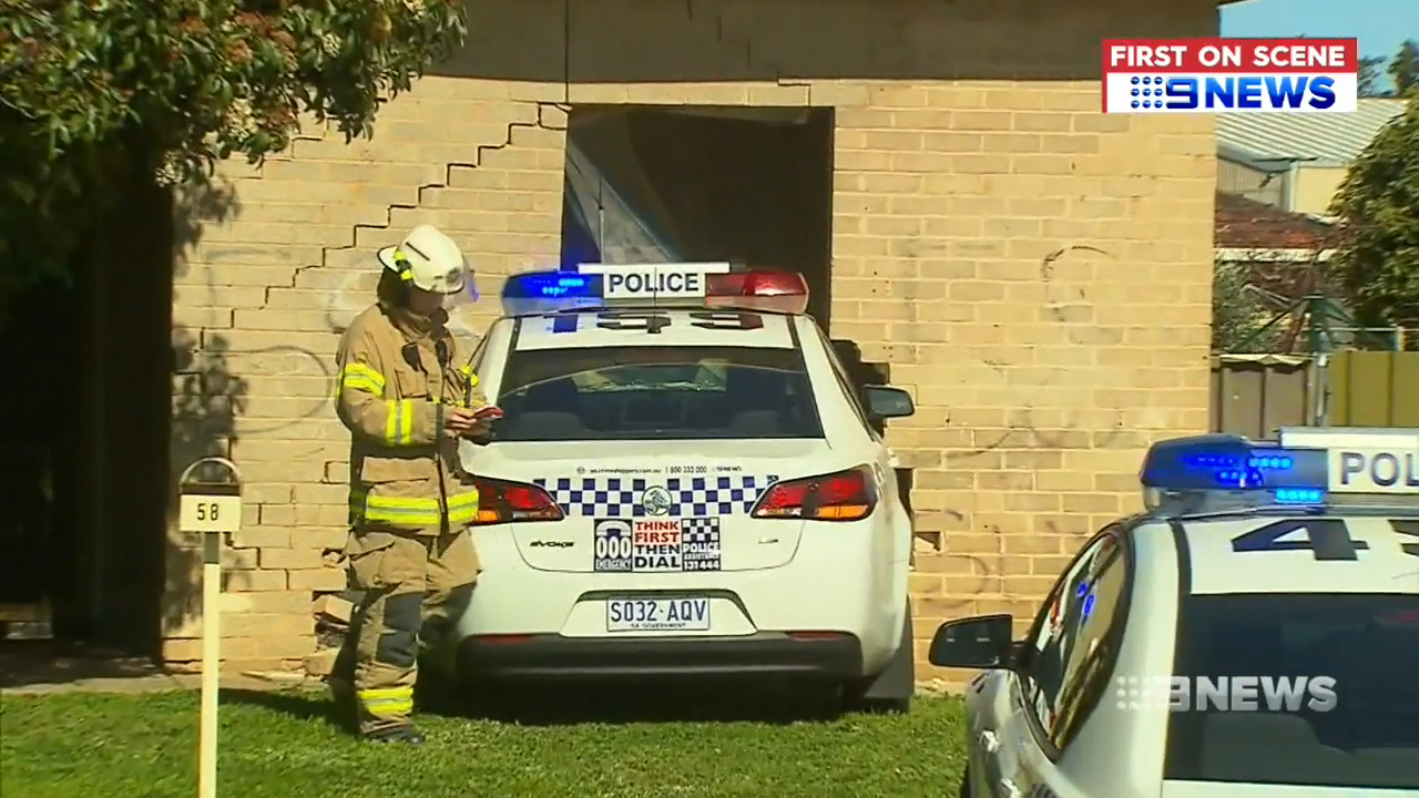 Police car ploughs into family home