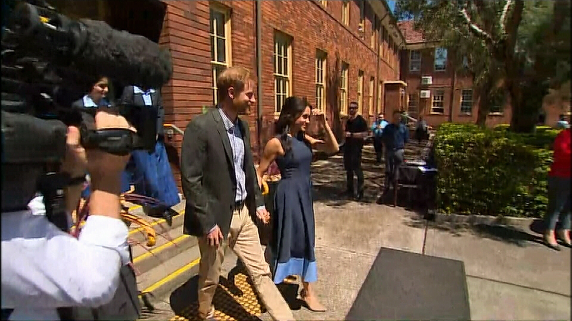 Prince Harry and Meghan arrive to crowd of cheering schoolgirls