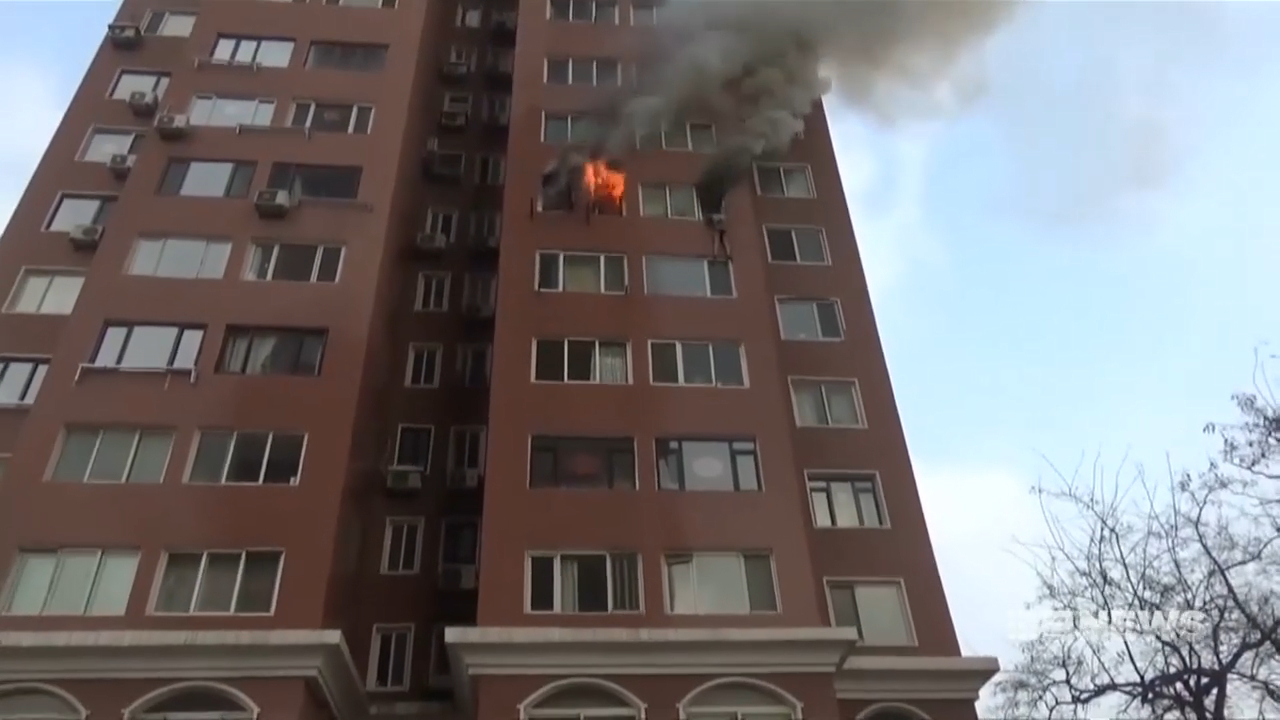 Woman hangs out eighth floor window of burning building