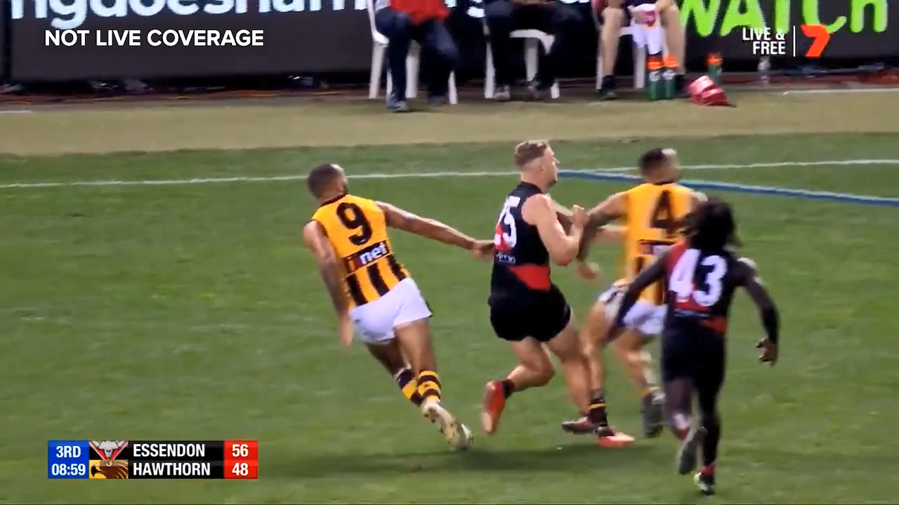 Essendon forward Jake Stringer limps off in the hands of the trainers after an ankle injury