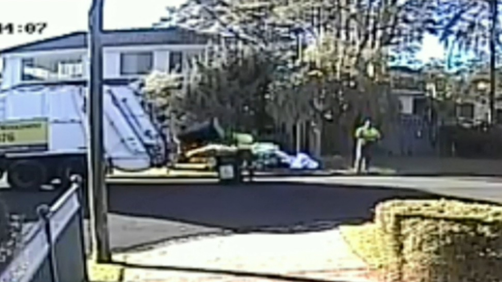 Workers toss recycling bins into garbage truck