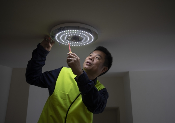 Dr Wen Hu checking one of the hallway lights meshed into the smart building network.