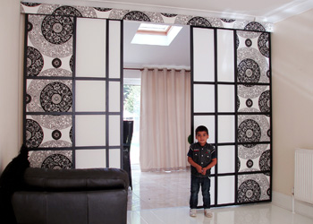 Boy Standing Next To Panel Blinds