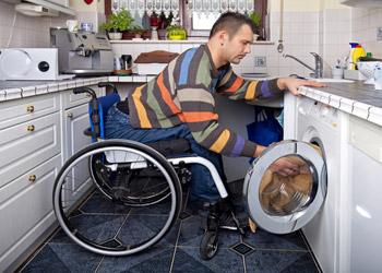 Gentleman In Wheelchair Washing Clothes