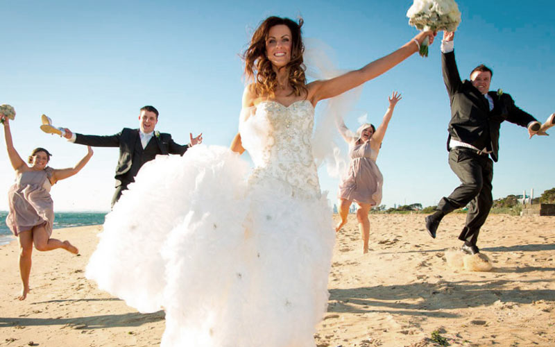 fun wedding photography of bridal party jumping on the beach at brighton