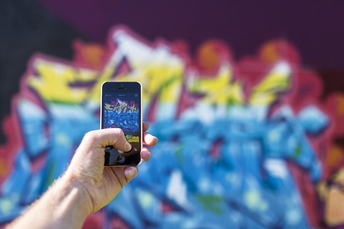 A hand holds a smartphone up to take a picture of some bright pink, yellow and blue graffiti on a wall. The hand and the smartphone are in sharp focus, while the wall behind it is blurred.