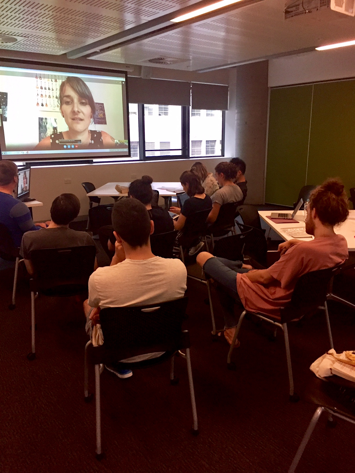 A classroom full of students watching a teacher on Skype.