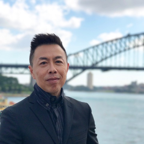 A portrait of Dr Tuck Wah Leong in front of the Sydney Harbour Bridge.