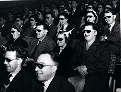 A black and white photo of a cinema audience wearing special glasses to watch a 3D film, taken during the 50s.