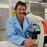 Dr Cathy Gorrie wearing a lab coat and using a microscope
