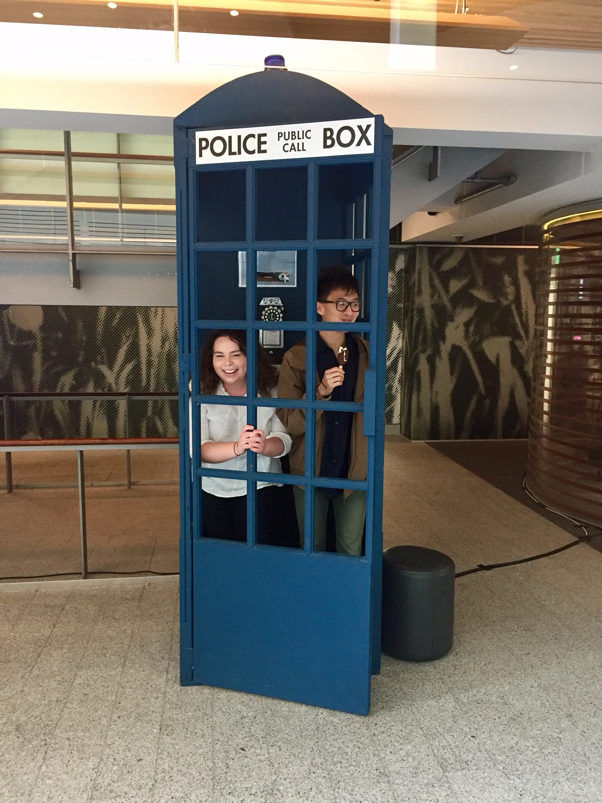 two students standing in a Tardis