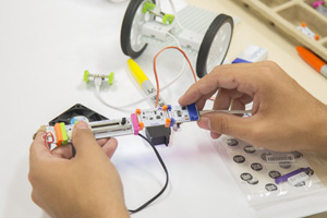 hands holding littleBits components over a white tablewith a partially assembled vehicle in the background